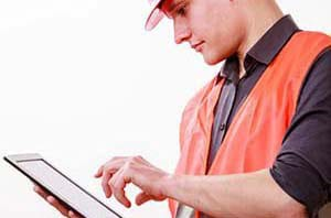 A construction worker using mobile construction management software to send time entry data to the back office.