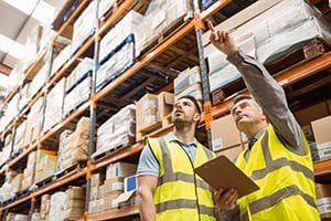 Warehouse managers using integrated wholesale distribution software to manage inventory.