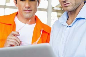 Two contractors using field service software to create a customer quote.